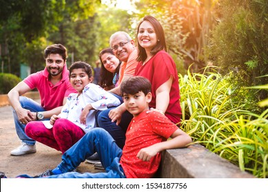Indian Family enjoying Picnic - Multi generation of asian family sitting over or near small wall in park, outdoor. selective focus