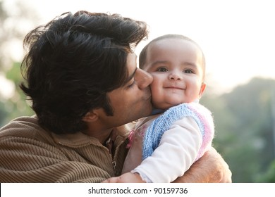 Indian family, father holding the daughter in his lap