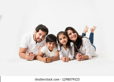 Indian family holding hands under chin, lying on white floor, selective focus
