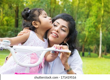 Indian family outdoor activity. Asian Mother teaching daughter cycling at the park in the morning. Child kissing parent.