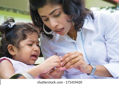 Indian family outdoor. Mother is comforting her crying daughter with injured finger.