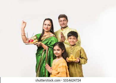 Indian family performing Puja of something in traditional cloths with lady holding Pooja thali while standing isolated over white background