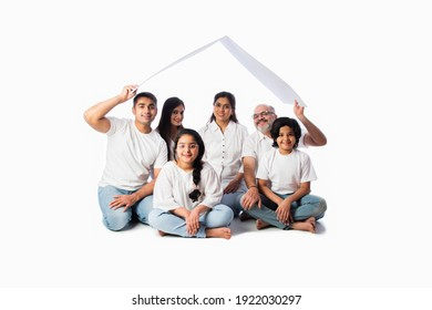 Indian family and real estate concept - Multigenerational asian family holding paper house model with keys against white background