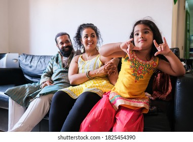 Indian family sitting on couch and enjoy time together - Parents and little child wearing traditional dress