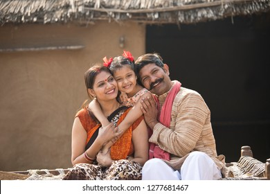 Indian family sitting on traditional bed in village