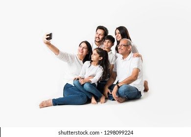Indian family taking selfie picture with smartphone while sitting on white background includes 3 generations. selective focus