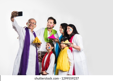 Indian Family taking selfie picture on Holi festival while holding sweets and colours