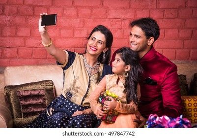 Indian family taking selfie with smartphone while sitting on Sofa, indoors