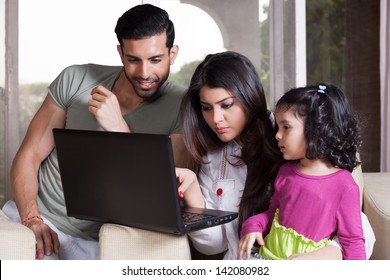 Indian family of three using laptop, young couple relaxing at home