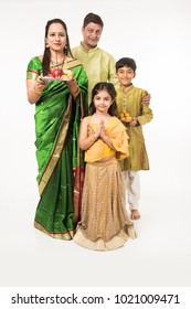 Indian family in traditional wear holding puja thali, standing isolated over white background