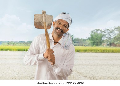 Indian farmer carrying hoe on his shoulder standing in field