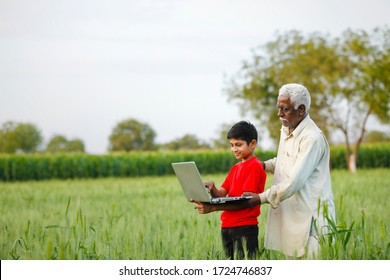 indian farmer with his grand son at wheat field, using laptop