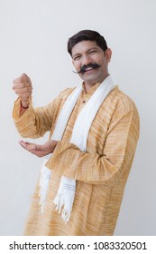 Indian farmer holding wheat in his hand and smiling