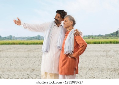 Indian farmer showing paddy field to his father