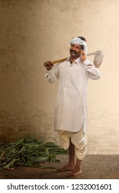 Indian farmer talking on mobile phone while carrying hoe on his shoulder