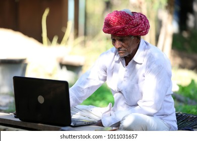 Indian farmer working on Laptop. Modern farmer of India. Tech Savvy Indian Grandpa. Indian Grandpa loves playing with laptop. Technology reaches rural India.Which laptop to buy for Seniors.