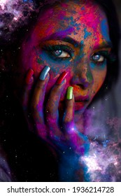 Indian fashion model with bright colorful mix of paint on her face. Creative art make up. Holi concept, blue eyes. neon fashion photography.