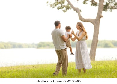 Indian Father and Caucasian Mother Playing with Young Son Outside in Nature