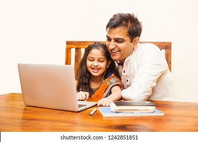 Indian father and daughter using laptop computer at home