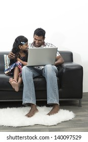 Indian Father and daughter working together on a laptop at home