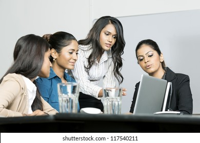 Indian female business colleagues working around a laptop