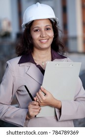 Indian female construction engineer holding clip boad
