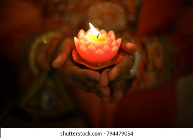 Indian female hands holding Diwali oil lamp.