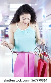 Indian female is looking into a shopping bag while standing in the mall