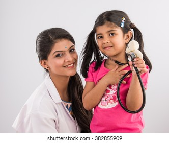 Indian female paediatric doctor holding a baby girl patient in her arms, isolated over white background