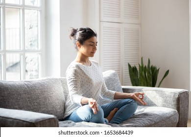 Indian female sitting on couch lotus pose put hands on lap folded fingers closed eyes enjoy meditation do yoga exercise at home. No stress, healthy habit, mindfulness lifestyle, anxiety relief concept