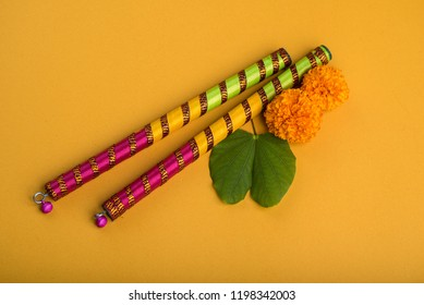 Indian Festival Dussehra and Navratri, showing golden leaf (Bauhinia racemosa) and marigold flowers with Dandiya sticks.