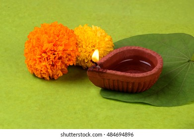 Indian Festival Dussehra, showing golden leaf and flowers with traditional diya on green background. Greeting card.