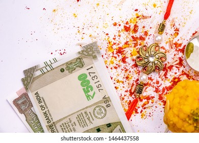 Indian Festival – Elegant Rakhi, sweet and Indian currency notes with scattered rice grains, kumkum, and turmeric on white backgro