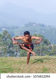 Indian fighter doing exercises with sword. Kalaripayattu marital art demonstration in Kerala, South India