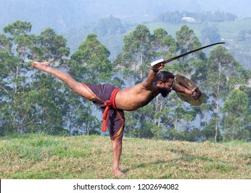 Indian fighter doing exercises with sword during Kalaripayattu marital art demonstration in Kerala, South India