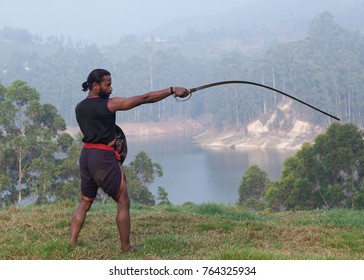 Indian fighter doing exercises with Urumi sword during Kalaripayattu marital art demonstration in Kerala, South India