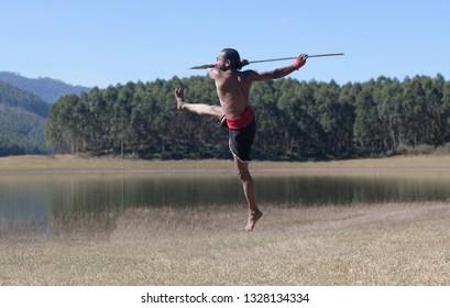 Indian fighter jumping up with lance - Kalaripayattu marital art demonstration outdoor in Kerala, South India