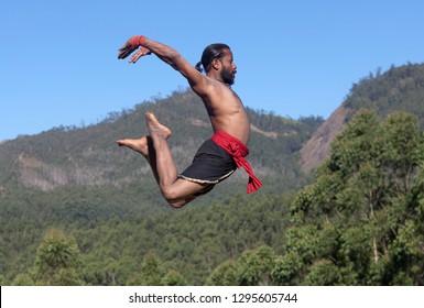 Indian fighter jumping up. Kalaripayattu Marital art demonstration in Kerala, South India