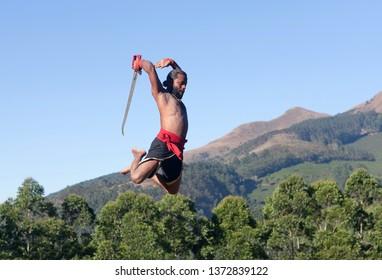 Indian fighter with sword jumping up during Kalaripayattu Marital art demonstration in Kerala, South India