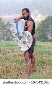 Indian fighter with sword and shield poses for a photo during Kalaripayattu marital art demonstration in Kerala, South India
