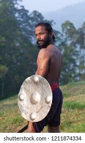Indian fighter witg sword and shield - Kalaripayattu marital art demonstration in Kerala, South India