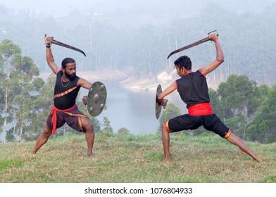Indian fighters performing Aayudha Payattu (Weapon Combat) during Kalaripayattu Marital art demonstration in Kerala, South India