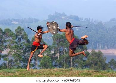 Indian fighters performing weapon combat during Kalaripayattu marital art demonstration in Kerala, South India