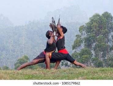 Indian fighters with sword and shield performing Aayudha Payattu (Weapon Combat) during Kalaripayattu Marital art demonstration in Kerala, South India
