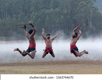 Indian fighters with swords jumping up during Kalaripayattu Marital art demonstration in Kerala, South India