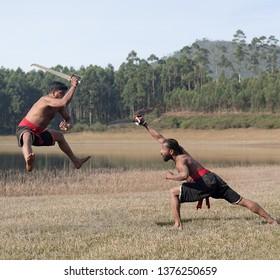 Indian fighters with swords performing Kalaripayattu Marital art demonstration in Kerala, South India