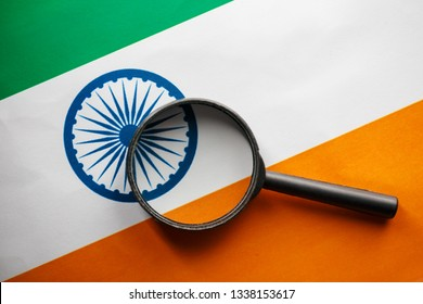 The Indian flag is visible through a magnifying glass. Spies and Observations for India India. Monitoring the state of India. War Terrorism Theft Concept