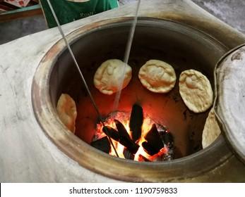 """Indian flat bread known as """"Naan"""" or """"Roti Nan"""" making in original India tandoori clay oven."""