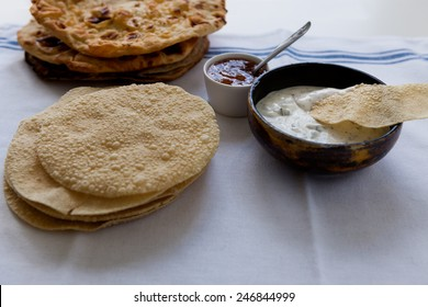 Indian flat breads poppadom and nan with mango chutney and dip sauce on the table