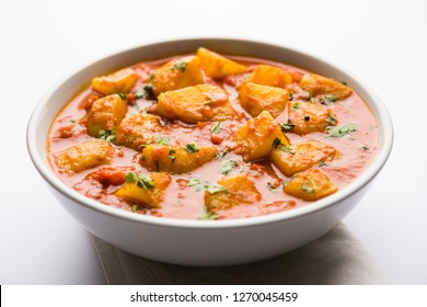 Indian food - Aloo curry masala. Potato cooked with spices and herbs in a tomato curry. served in a bowl over moody background. selective focus